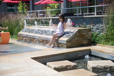 Philadelphia, Pennsylvania June 16 2018: Little girl playing water at the fountain in Philadelphia mall