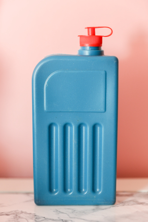 Front view of black ink bottle with red cap isolated on pink wall.
