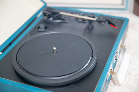 Vintage blue record player on the carpet floor.