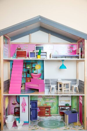 A Child's doll house with furniture on a yellow background-Image