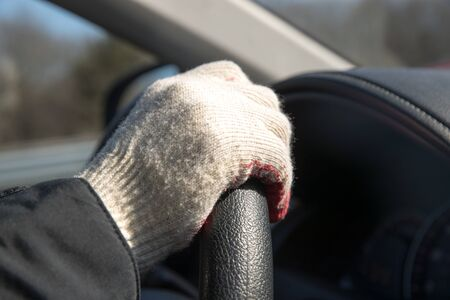 The hands of the driver in gloves, driving a moving car. 写真素材