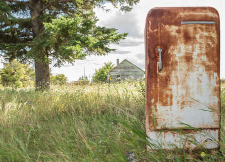fridge: horizontal image of an very old rusted fridge sitting outside in the grass in the summer time.
