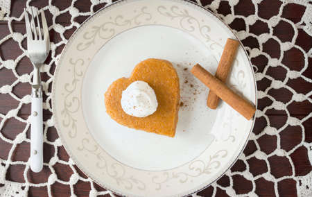 dollop: horizontal image of a heart shaped piece of pumpkin pie with a dollop of whipped cream in a white plate with cinnamon sticks placed on a white lace doily. Stock Photo
