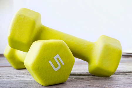 lb: horizontal close up image of a pair of 5 lb lime green dumbbells on wood surface with white background.