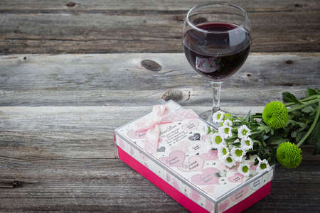 room for text: horizontal image of a glass of wine sitting beside a decorated valentine box of candy with an old vintage wood background with room for text.