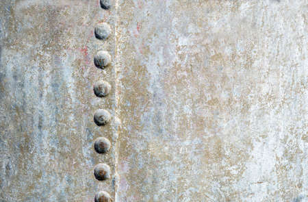 one sheet: full background image of silverbrown sheet metal with a seam on one side with button like steel pegs down the side of the seam with room for text. Stock Photo