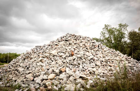 heaped: horizontal image of a large pile of rocks heaped up to a peak under a very cloudy grey sky in the summer with room for text. Stock Photo
