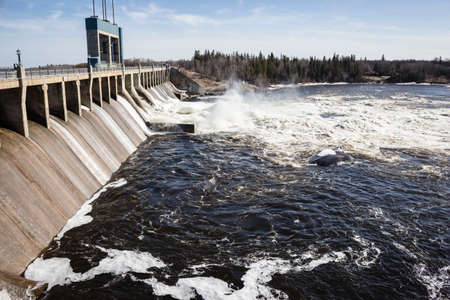 aggressively: horizontal image of a large hydro dam with water churning aggressively over the turbines in the summer time. Stock Photo