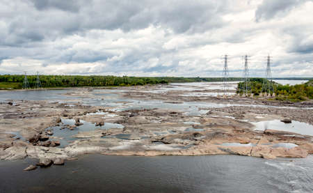 receded: horizontal image of vastly receded lake close to an electricity dam with flat rock and shale exposed with electricity towers in the background under a very cloudy sky in the summer.