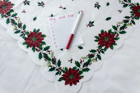 flower decoration: horizontal image of a white tablecloth with christmas flowers along the edges and a piece of paper lying on top saying my wish list Stock Photo