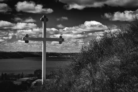 knoll: horizontal black and white low key image of a cross sitting beside a grassy knoll with a lake in the background in the summer time.