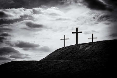 lit image: black and white filtered image of a silhouette of three crosses standing on hill with the sky lit up in the background a bright white light Stock Photo