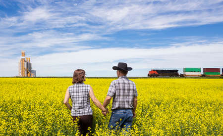 agronomist: horizontal image of a husband and wife checking canola field while a train rumbles by in the background next to a grain elevator.