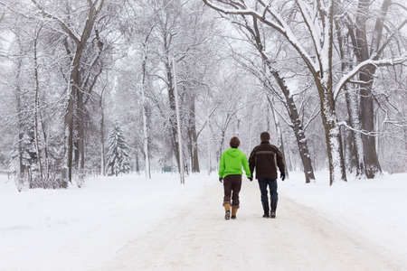 mild: horizontal image of a man and woman walking hand in hand down a path with trees on either side on a mild winter day Stock Photo