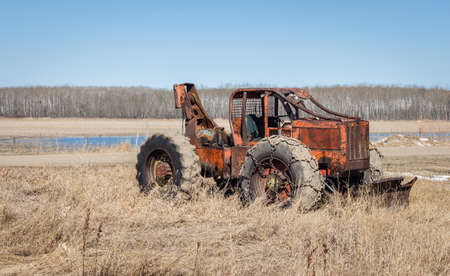 heavy chains: horizontal image of an orange antique heavy duty loader with a winch in the back  and big chains around the wheel and a blade in the front.
