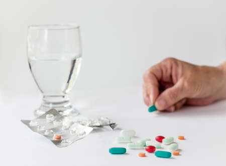 reliever: medication and pills with a glass of water and a hand holding a pill isolated on white background.