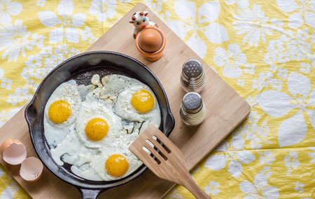cast iron pan: horizontal image of four fried eggs in a cast iron pan sitting on a wooden chopping block with wood spatula and salt and pepper shakers with a white and yellow background