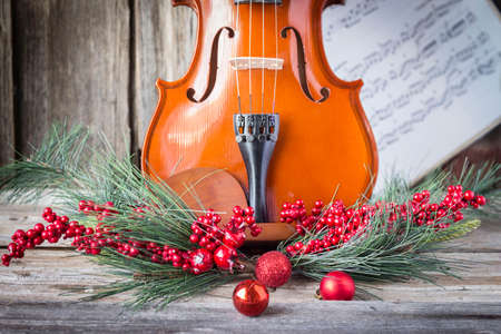 adorning: horizontal image of the bottom half of a violin with sheet music and christmas fern and cranberries adorning the front of the fiddle on rustic wood background.