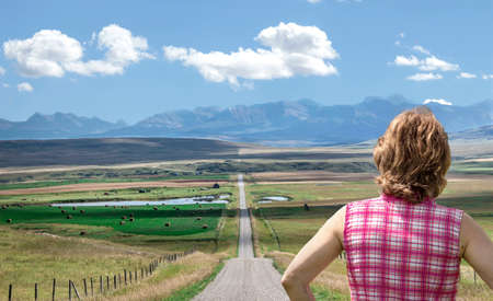 end of a long day: horizontal close up image of caucasian woman with back facing the camera standing at the end of a long straight dirt road her gaze on the mountains in the distance on a beautiful summer day.
