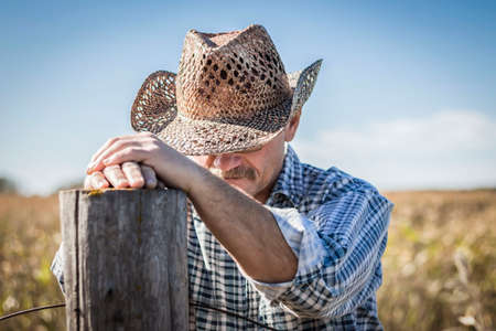 bowed head: horizontal close up image of a caucasian cowboy praying by a fence post on a warm fall day.