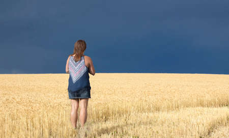 storm coming: horizontal image of a caucasian woman standing in a field of golden wheat looking toward the sky which is very dark with a thunder storm coming.