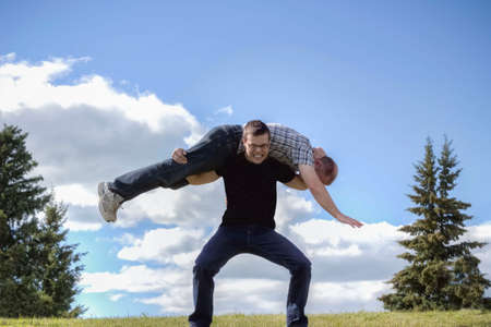 well head: horizontal image of a well built caucasian teen age guy carrying his dad across his shoulder gritting his teeth in the summer with a blue sky  over head.