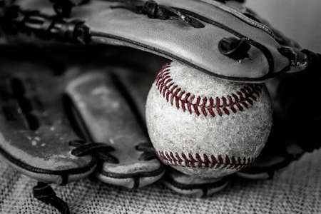 catcher's mitt: horizontal close up black and white vintage image of an old worn baseball  with red thread and catchers mitt. Stock Photo