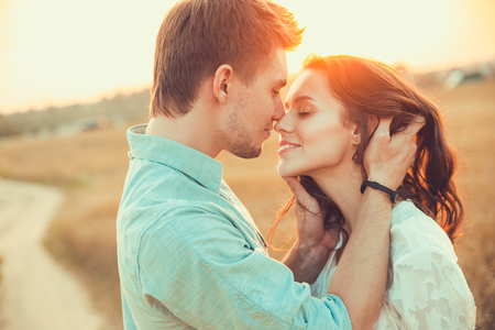 hugs and kisses: Young couple in love outdoor.Stunning sensual outdoor portrait of young stylish fashion couple posing in summer in field