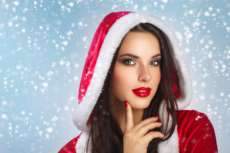 Beautiful young woman in Santa Claus clothes over Christmas background. Smiling woman holding cristmas gift over winter snowflakes background. beauty portrait . face closeup .Studio shot