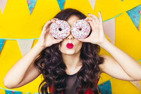 Beauty girl taking colorful donuts. Funny joyful woman with sweets, dessert. Diet, dieting concept. Junk food, Celebration and party.