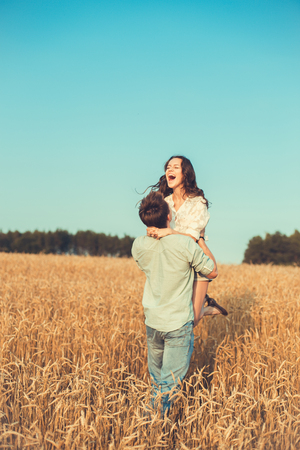 Young couple in love outdoor.d.Couple hugging.Young beautiful couple in love staying and kissing on the field on sunset. Soft sunny colors.