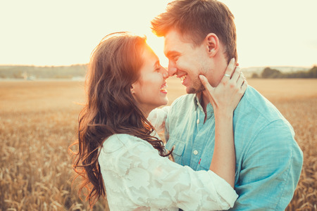 Young couple in love outdoor. Stunning sensual outdoor portrait of young stylish fashion couple posing in summer in field. Happy Smiling Couple in love. They are smiling and looking at each other Stockfoto