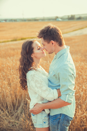 Young couple in love outdoor. Stunning sensual outdoor portrait of young stylish fashion couple posing in summer in field. Happy Smiling Couple in love. They are smiling and looking at each other 免版税图像