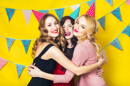 Portrait of joyful friends toasting and looking at camera at birthday party. Attractive friends celebrating a birthday. Smiling girls. Celebration and party. Having fun. Stock Photo