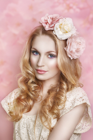 Glamour portrait of beautiful woman model with fresh daily makeup and romantic wavy hairstyle. Fashion shiny highlighter on skin, sexy gloss lips make-up and dark eyebrows on pink  background. Magnificent portrait of a beautiful young woman with perfect s