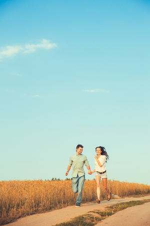 Young couple in love outdoor.Stunning sensual outdoor portrait of young stylish fashion couple posing in summer in field photo