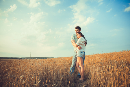 Young couple in love outdoor. Stunning sensual outdoor portrait of young stylish fashion couple posing in summer in field. Happy Smiling Couple in love. They are smiling and looking at each other photo