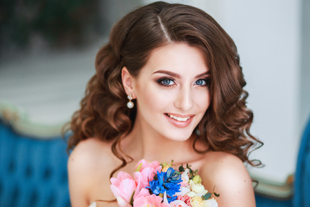 Beautiful young bride with wedding makeup and hairstyle indoor .Closeup portrait of young gorgeous bride in studio
