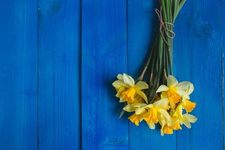 Geel gele narcissenboeket op blauwe houten achtergrond, Pasen-kaart. Plaats voor tekst. Bloemenachtergrond
