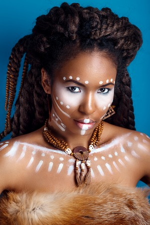 African style . Attractive young woman in ethnic jewelry . close up portrait of a woman with a painted face. Creative makeup and bright style.