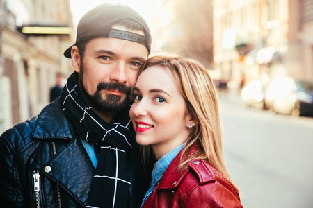 Outdoor fashion portrait of stylish sexy couple kissing on sunset at the city street, wearing biker leather total black rock n roll look Stock Photo