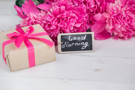 Pink peony flowers,gift box and notes good morning on white rustic table from above, breakfast on Mothers day or Womens day .Summer flowers bouquet Stock Photo - 80554533