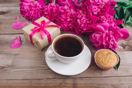나무 배경에 커피, 핑크 모란 패턴의 컵. 좋은 아침. 여자 또는 어머니의 날 배경. 평면도
