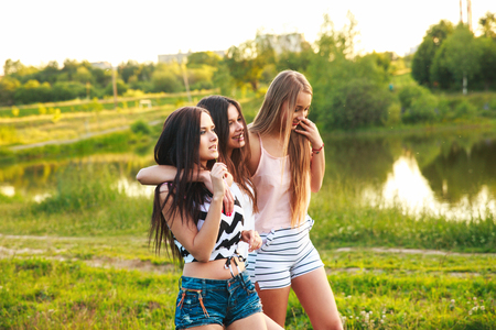 three beautiful girls walking and laughing on sunset in the park. Friendship concept.