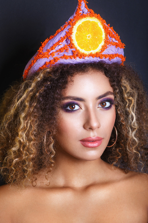 african american woman: Young black woman with afro hairstyle and make up . Ethnic woman with flower and fruit diadem. Studio shot.