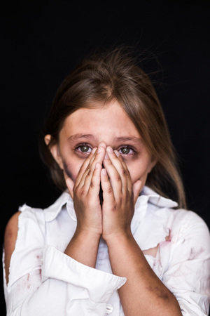close-up portrait of a little girl crying and covering her face isolated on black. Child abuse
