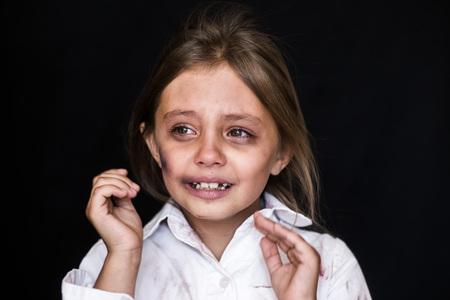 Kindermishandeling. Verdrietig en eenzaam meisje huilt. Gewond kind poseren als slachtoffer van huiselijk geweld