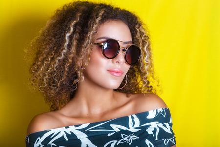 portrait à l'intérieur d'une jeune femme américaine afro à lunettes de soleil. Fond jaune Mode de vie.