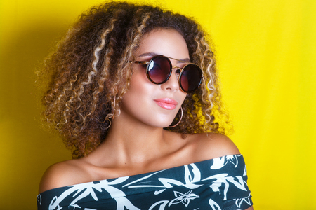 portrait indoors of a young afro american woman in sunglasses. Yellow background. Lifestyle.