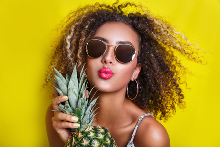 Fashion summer portrait afro american girl in sunglasses and pineapple over yellow background